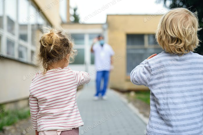 Children waving at father doctor in front of hospital, coronovirus and isolation concept