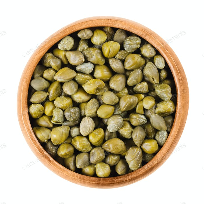 Capers in wooden bowl on white background