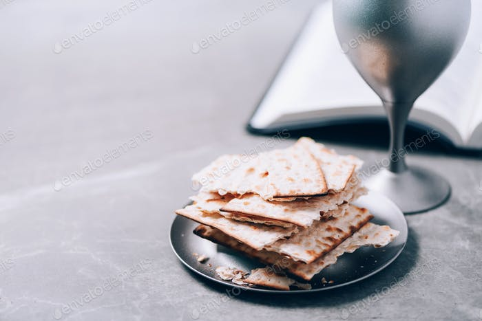 Unleavened bread, chalice of wine, Holy Bible on grey background. Christian communion for reminder