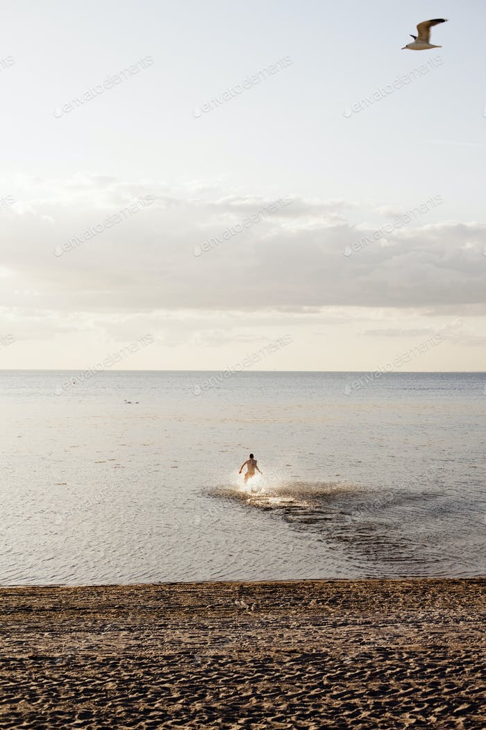 Distant image of man running in sea