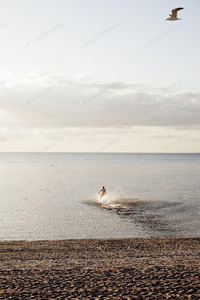 Ferne Bild des Menschen läuft im Meer