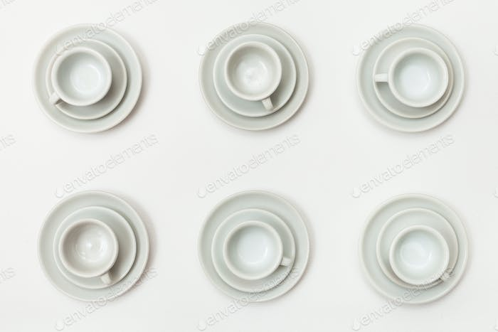 top view of six white cups and saucers on white