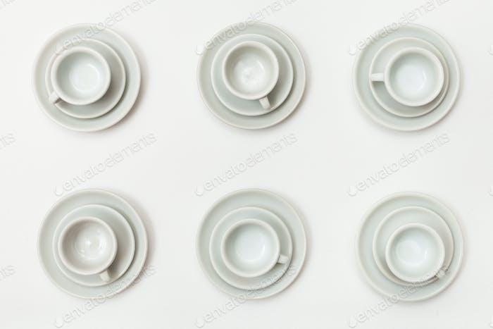 Draufsicht von sechs weißen Tassen und Untertassen auf weiß