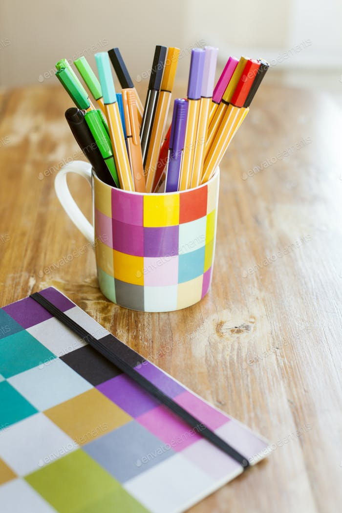Marker and felt tip pens in desk organizer by book on wooden table