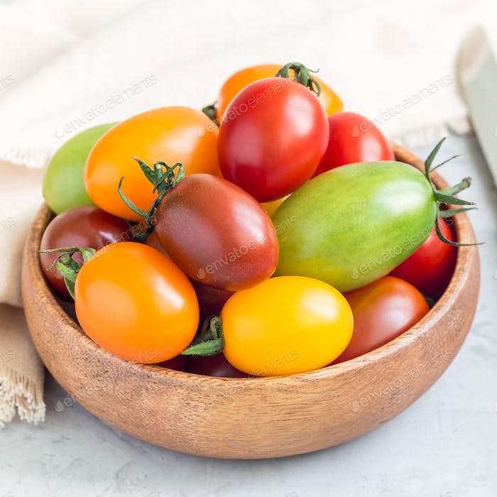 Small colorful cherry tomatoes in wooden bowl on table, square format