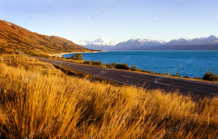 Country Road With Amazing Scenery Of Lake And A Mountain Range