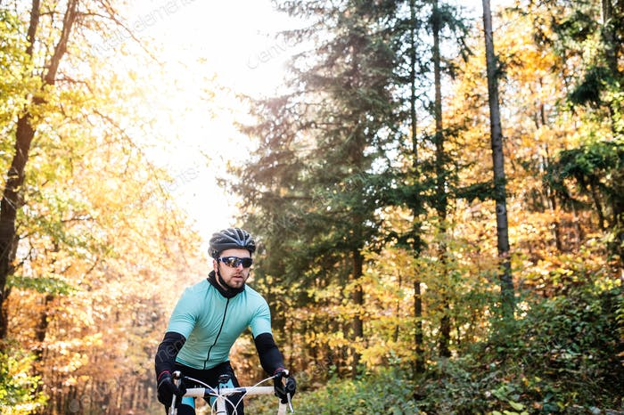 Young sportsman riding bicycle outside in sunny autumn nature