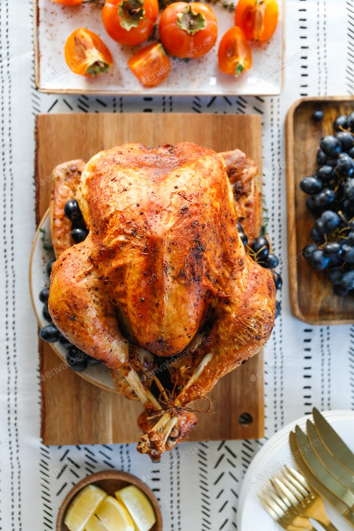 Roasted whole turkey on a table with persimmon, blue grape and lemon