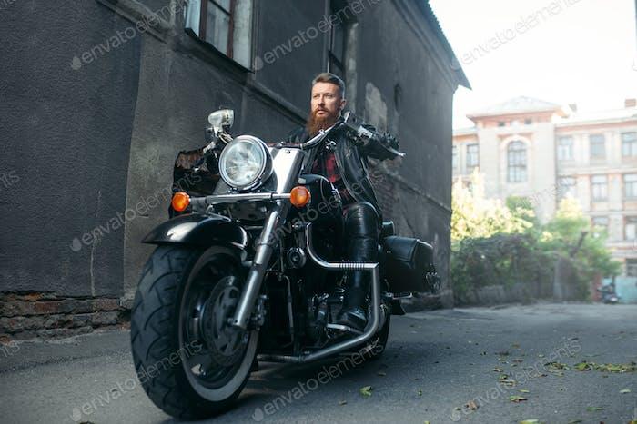 Bearded motorcyclist on classical chopper, biker