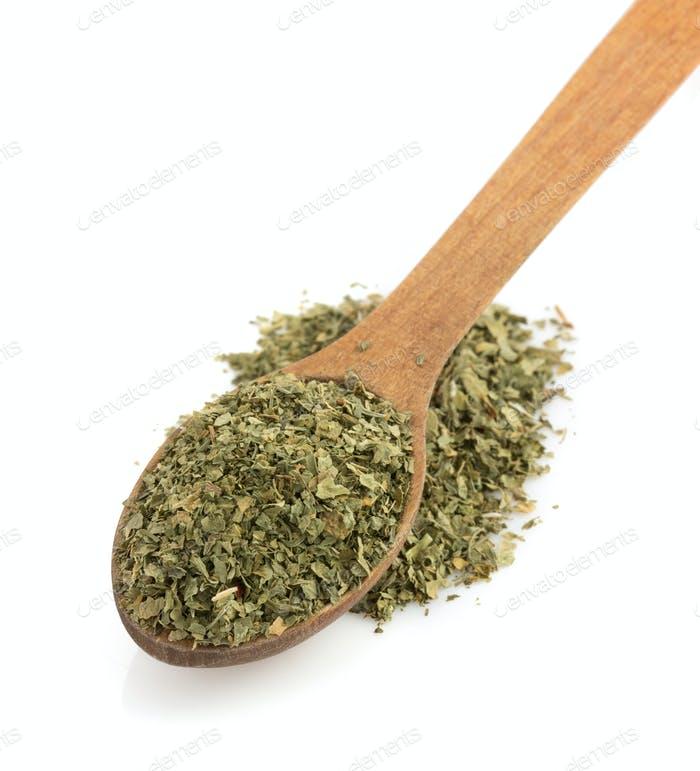 dried green spices and spoon on white