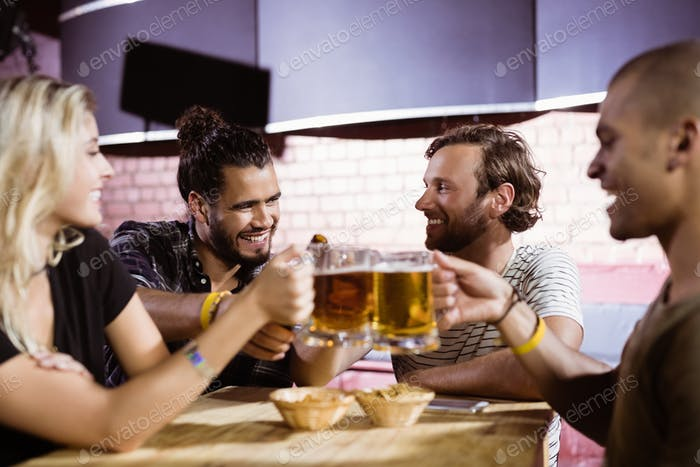 Happy friends toasting beer mugs at nightclub