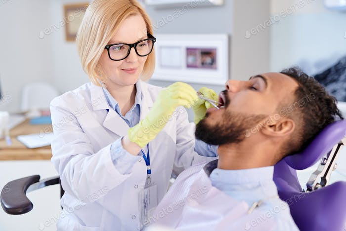 Blonde Female Dentist Working with Patient