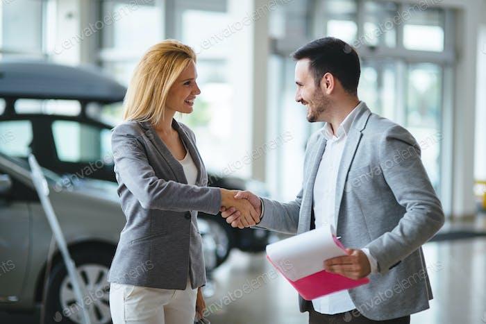 Handsome salesman at car dealership selling vehichles