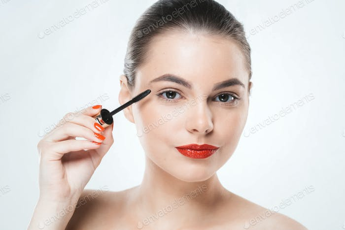 Mascara makeup woman face with red lips and manicure nails isolated on white