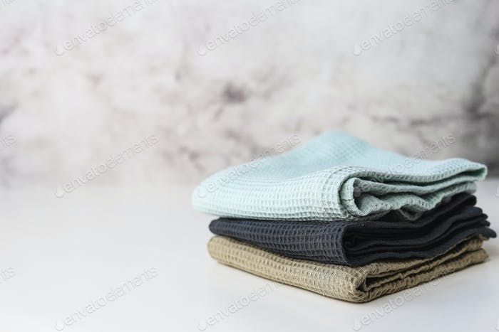 Stack kitchen cotton towels on gray background
