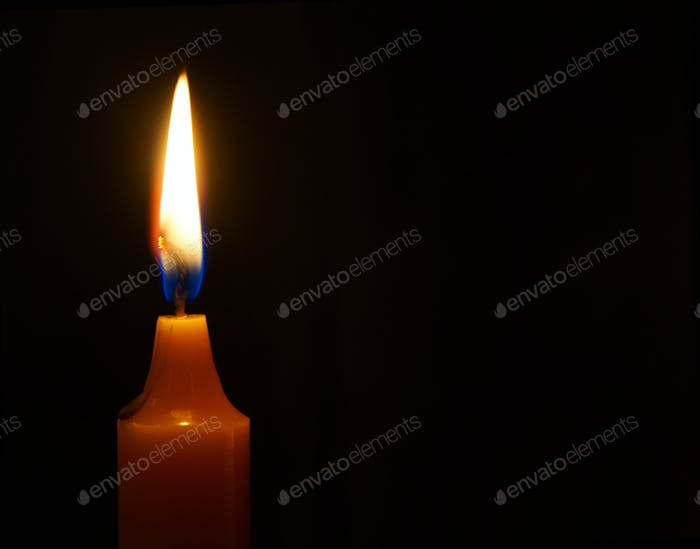 Brennende Kerze auf schwarzem Hintergrund.
