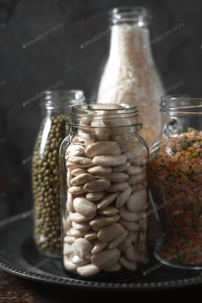 Lentils, white beans, rice in glass bottles