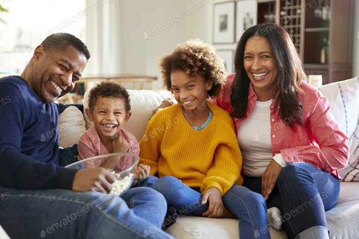 Youthful grandparents sitting with their grandchildren on sofa in the living room
