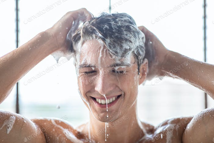 Handsome young male model washing hair with shampoo
