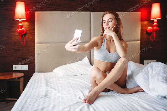 Pretty woman sitting in bed and makes selfie