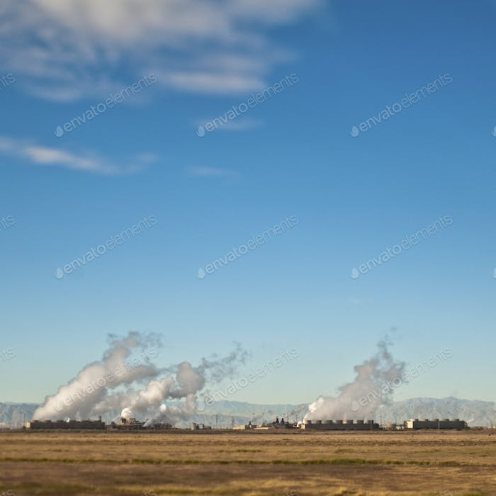 49647,A row of buildings and plumes of white smoke viewed across flat land, with mountains behind.