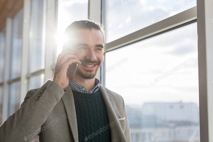 Business Man Talking On Mobile Phone Call Standing in front Panoramic Window Businessman In