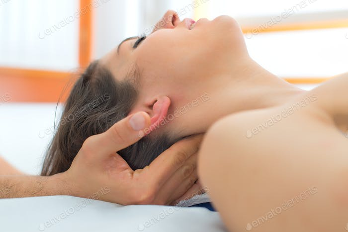 Therapist massaging the neck of woman
