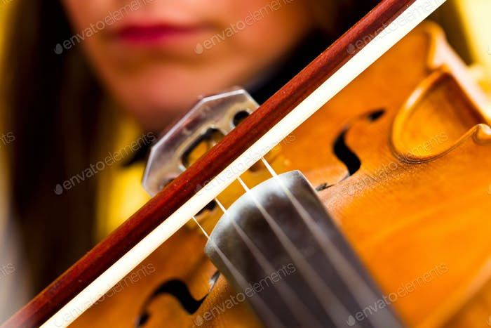 Girl playing the violin classical music concert