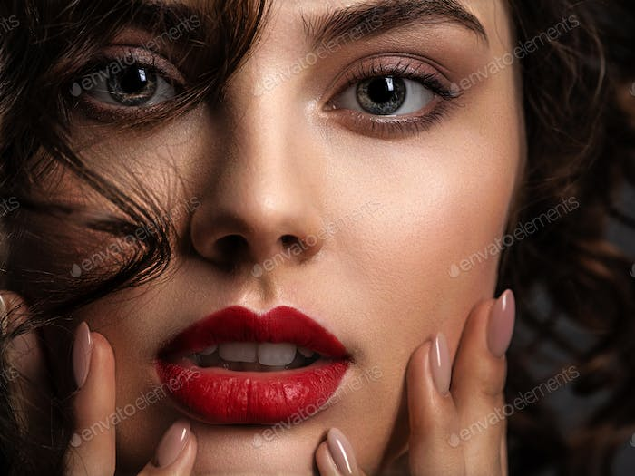 Face of a beautiful woman with a smoky eye makeup and red lipsti
