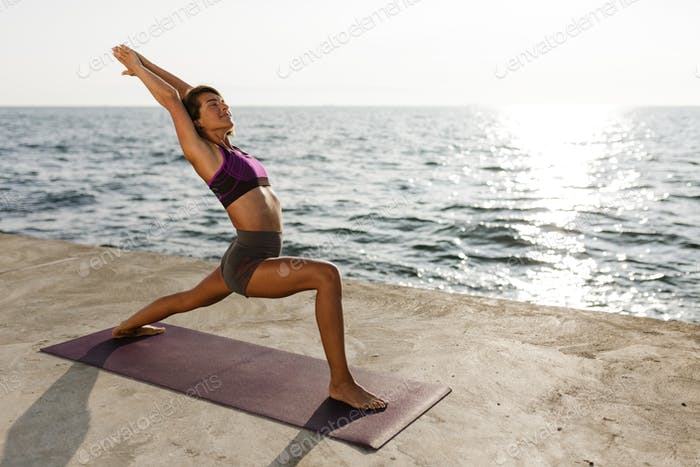 Young happy woman standing and training yoga poses by the sea