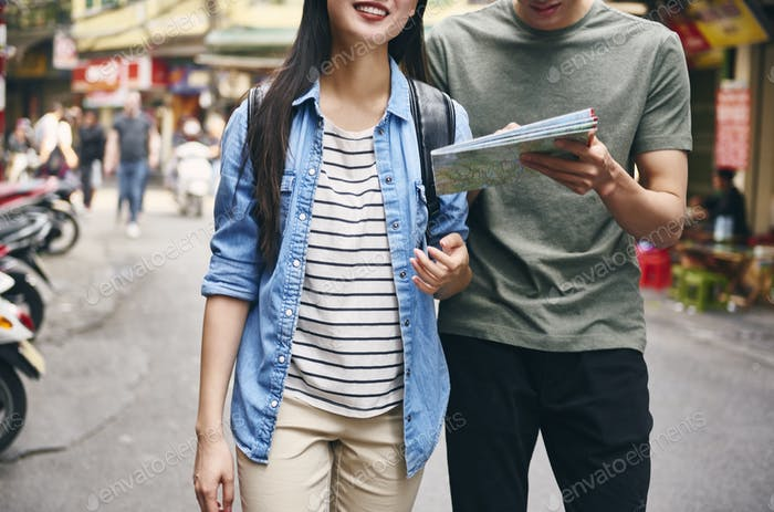 Couple of tourists using map while sightseeing