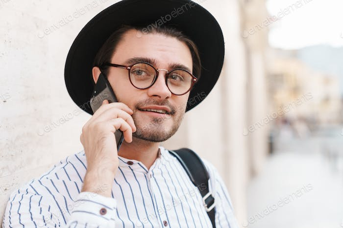 Photo of pleased caucasian man talking on cellphone while leaning on wall in city street