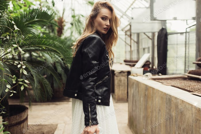 Young gorgeous woman in black leather jacket and white dress dre