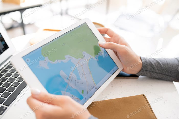 Hands of young female student holding digital tablet with map on display