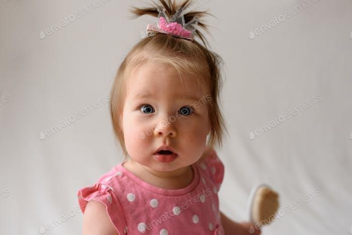Niña pequeña con un vestido rosa se sienta con un peine en la mano sobre un fondo blanco.