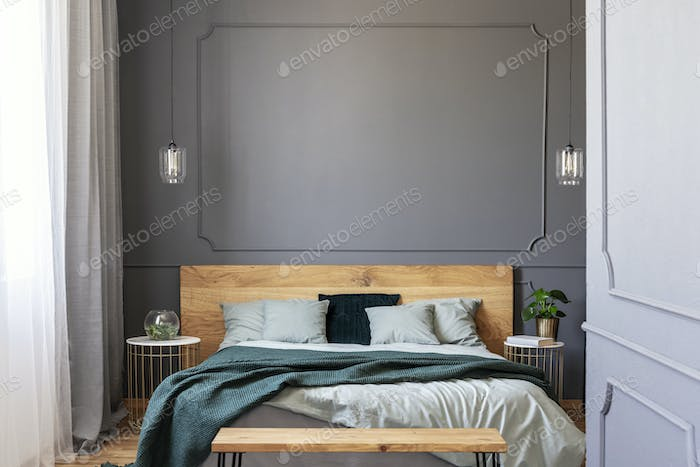 Green blanket on wooden bed with pillows in grey bedroom interio