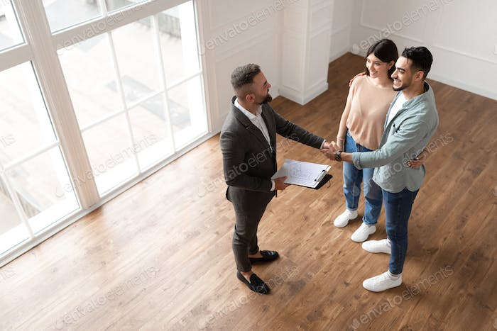 Couple Buying New Apartment, Shaking Hands With Realtor