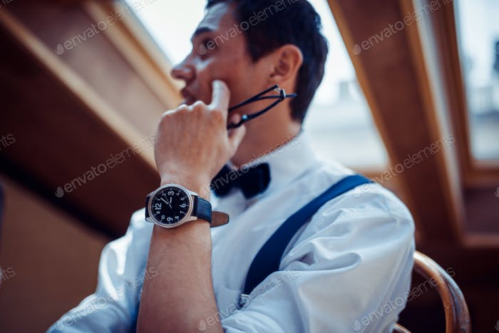 Elegant young man in suspenders and glasses in cafe