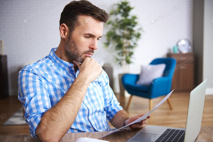 Focused businessman reading important documents at his desk