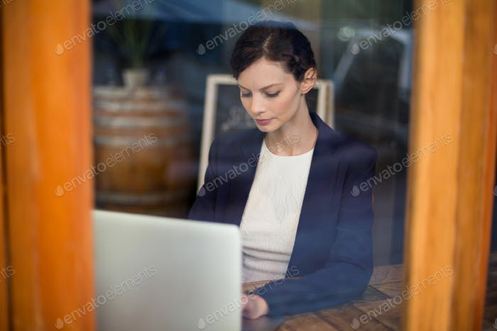 Businesswoman using laptop in cafe