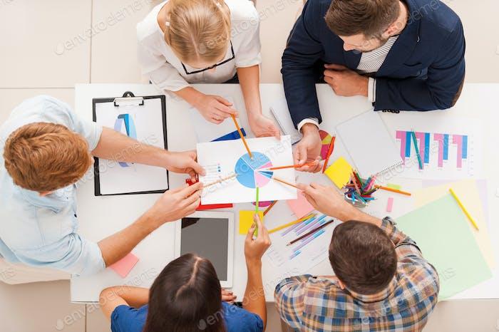 Discutiendo el diagrama. Vista superior de gente de negocios apuntando diagrama juntos mientras se sienta en la mesa