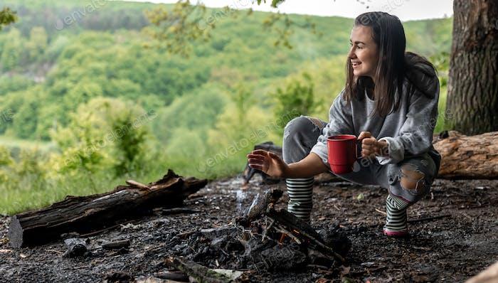 Mädchen mit einer Tasse heißem Getränk in der Nähe des Feuers in der Natur.