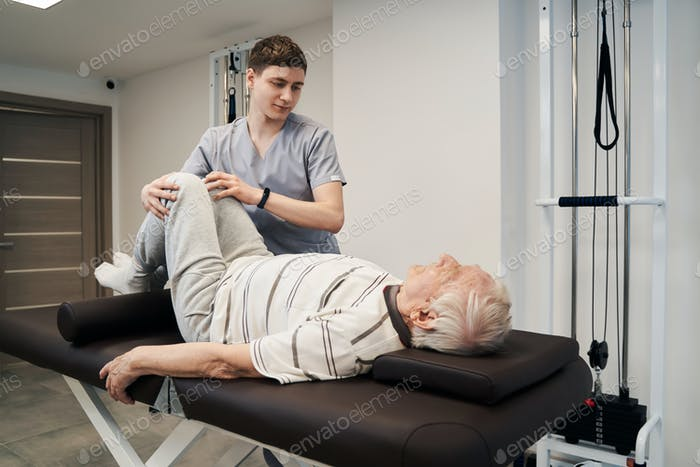 Orthopedic surgeon providing exercise therapy to aging patient