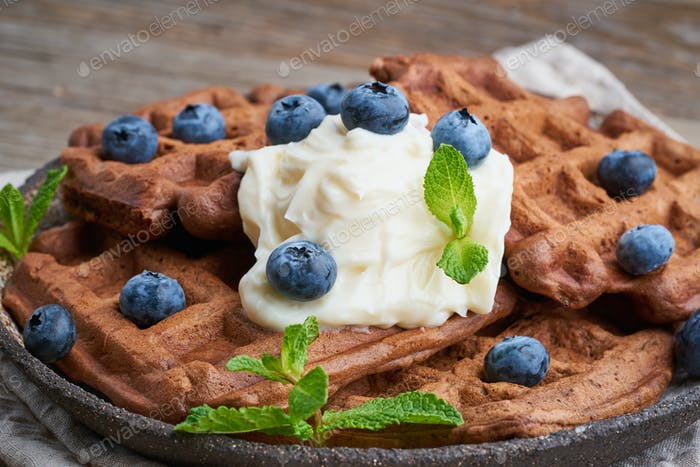 Chocolate banana waffles with blueberries, on dark wooden old table. Side view, close up