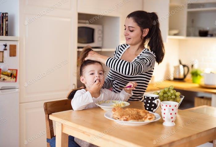 Little girl eating breakfast, mother doing her hair