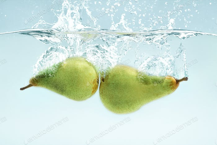 Vitamin freshness. Green pears flying into transparent water on blue background