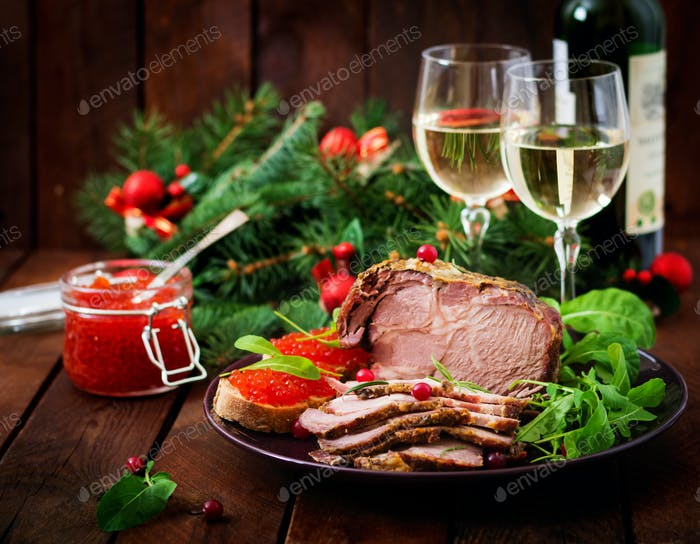 Christmas baked ham and red caviar, served on the old wooden table.
