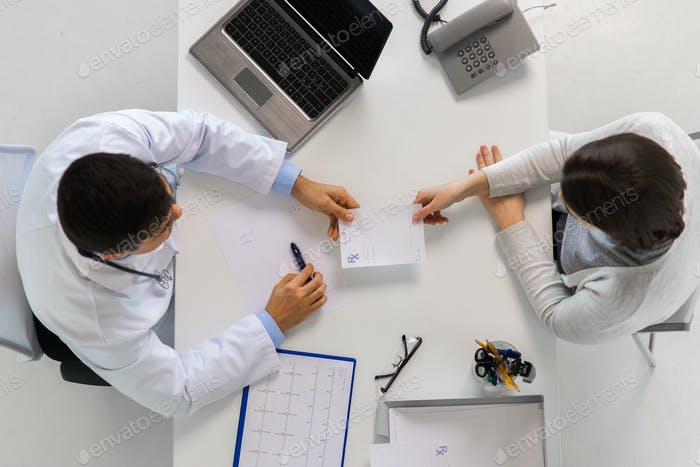 doctor giving prescription to patient at hospital
