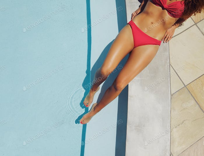 Young woman relaxing on edge of a pool