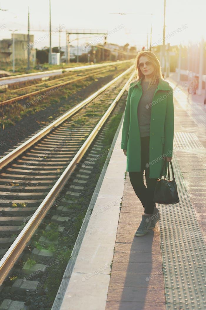 Erstaunliche blonde Frau wartet auf einen Zug